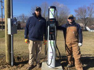 VEC's Gabe Durham, and John Schoeder stand beside the new dual point EV charging station.